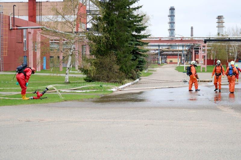 De professionele brandbestrijders in oranje vuurvaste kostuums in witte helmen met gasmaskers testen brandslangen en brandkanonne royalty-vrije stock afbeelding