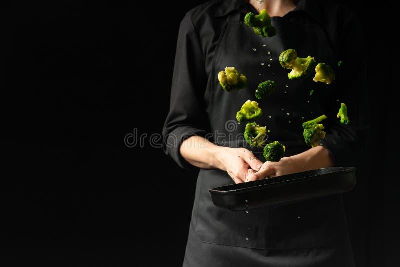 De professionele chef-kok bereidt broccoli voor Kokend groenten en voedsel op een donkere achtergrond Foto van het hotel Horizont royalty-vrije stock foto's