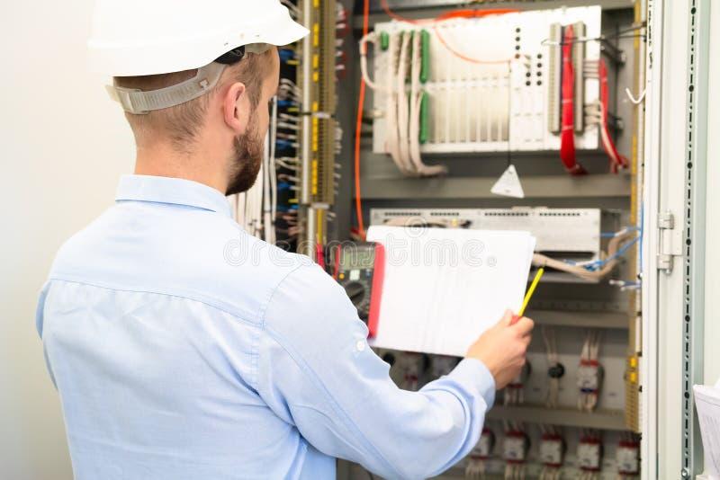 De professionele elektricien in bouwvakker leest elektrische regeling dichtbij controlebord op hulpkantoor stock fotografie