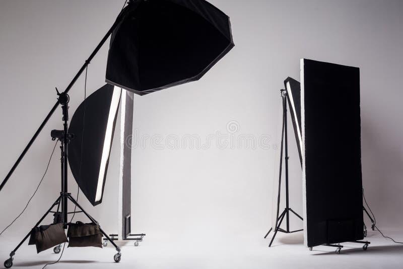 De professionele fotostudio met lichte opstelling omvatte achthoek softbox op boom, strook zachte doos en reflector op lichtgrijz stock afbeeldingen