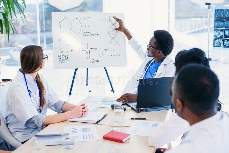 De professionele groep multi rassenartsen of de internen met mentor hebben een vergadering en het maken van nota's bij het zieken stock foto