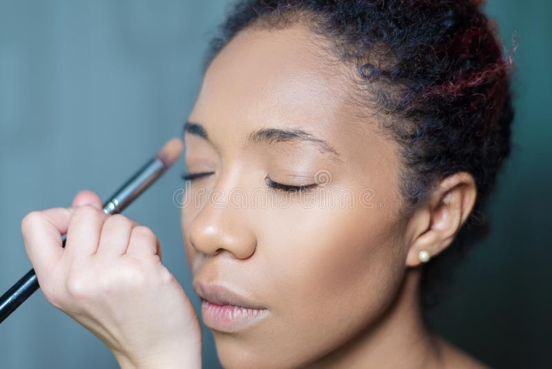 De professionele kunstenaar van de samenstellingsmake-up past make-up op een donker-gevilde vrouw toe stock afbeeldingen