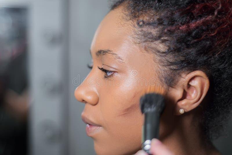 De professionele kunstenaar van de samenstellingsmake-up past make-up op een donker-gevilde vrouw toe stock fotografie