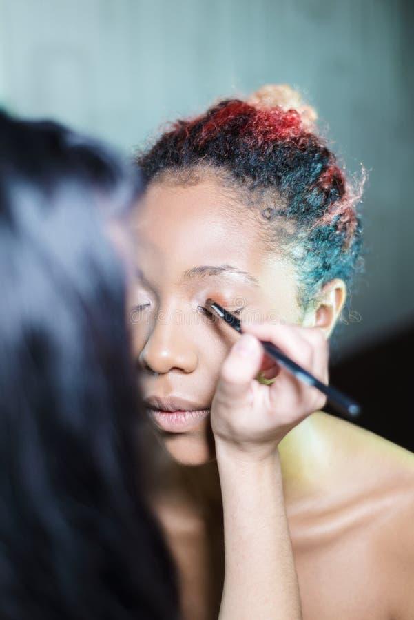 De professionele kunstenaar van de samenstellingsmake-up past make-up op een donker-gevilde vrouw toe stock foto
