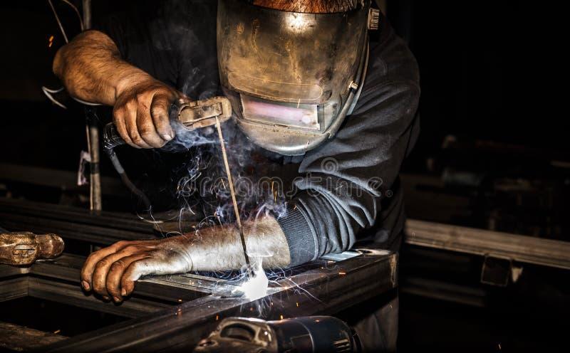 De professionele lasser in masker last staal met elektrisch toortshulpmiddel royalty-vrije stock fotografie