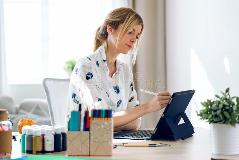 De professionele mooie jonge tekening van de ontwerpervrouw iets op haar digitale tablet op het kantoor royalty-vrije stock afbeelding