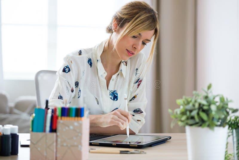De professionele mooie jonge tekening van de ontwerpervrouw iets op haar digitale tablet op het kantoor stock foto's