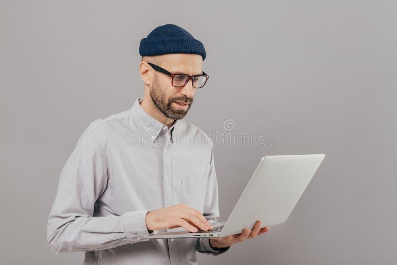 De professionele IT ontwikkelaar downloadt dossiers, babbelt online in sociale netwerken, bloggs en surfes Internet-webpagina's d royalty-vrije stock afbeelding