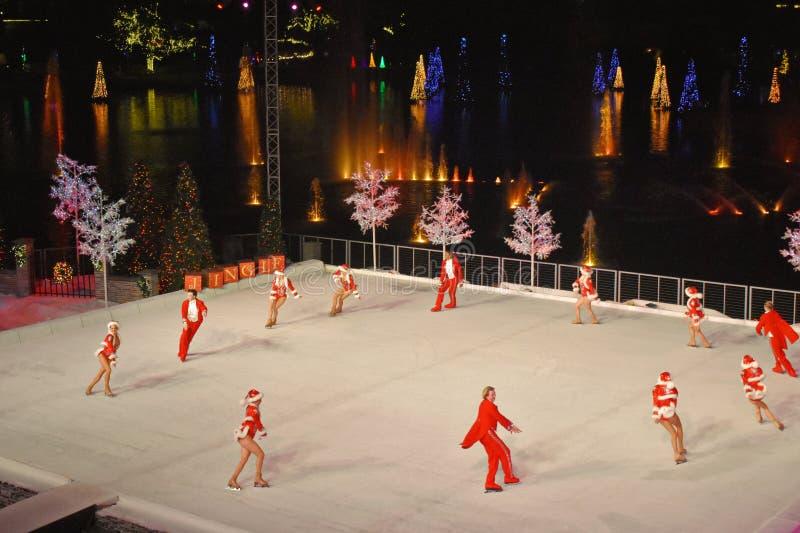 De professionele Schaatsers die een ronde doen tijdens Kerstmis tonen op ijs bij nacht op Internationaal Aandrijvingsgebied royalty-vrije stock fotografie