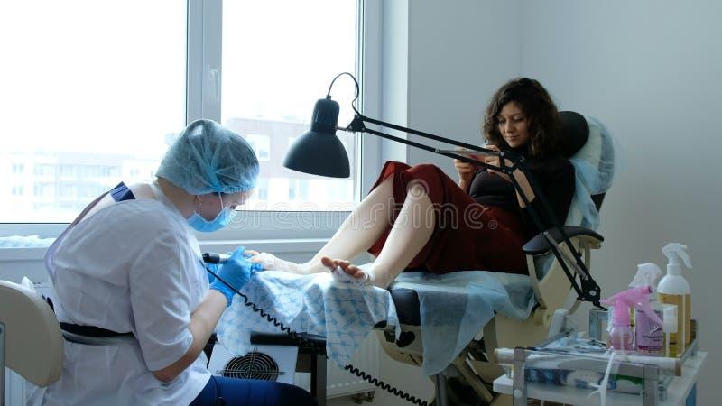 De professionele schoonheidsmeester voert pedicure met machine uit stock foto's