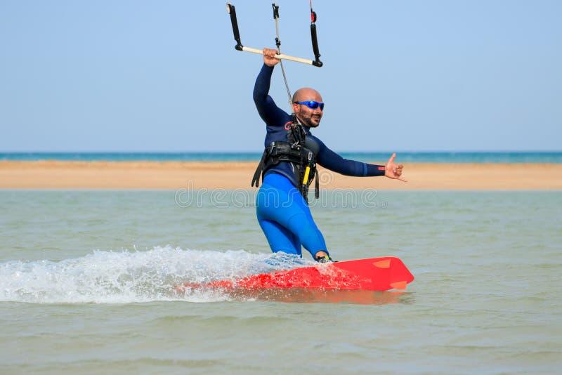 De professionele sportman van de vlieger inschepende ruiter met vlieger berijdt blauwe lagune glimlachend genietend de vrije tijd royalty-vrije stock afbeeldingen