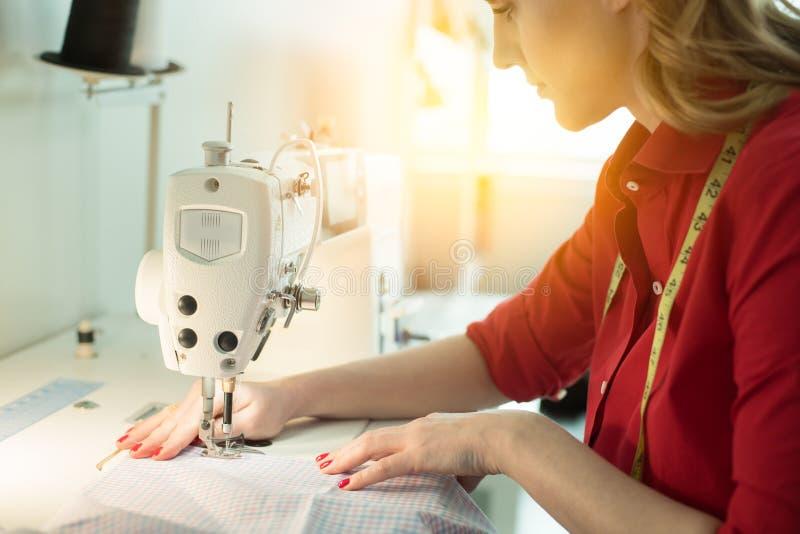 De professionele vrouw die van de kleermakersontwerper nieuwe rok op naaimachine naaien royalty-vrije stock afbeeldingen