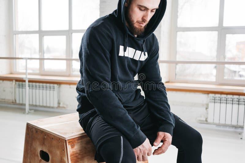 De professionele zitting van de trainingsportman op doos in sporthal stock foto