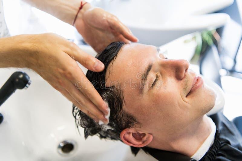 De profielmening van een jonge mens die zijn haar krijgen waste en zijn die hoofd in een haarsalon wordt gemasseerd stock foto