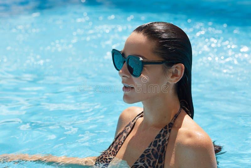 De profielmening van mooie overweldigende elegante donkerbruine modelvrouw met perfect gezicht zwemt binnen kostuum met luipaardd royalty-vrije stock afbeelding