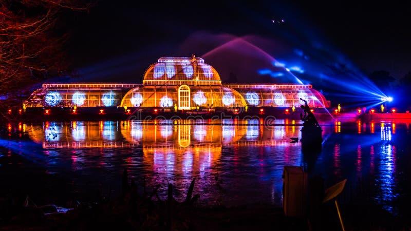 De projectie van de nachtlaser met gekleurde bezinningen over het water stock afbeeldingen