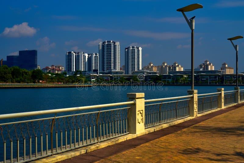 De promenade van het Putrajayameer met woonwijk en wolkenkrabbers stock afbeelding