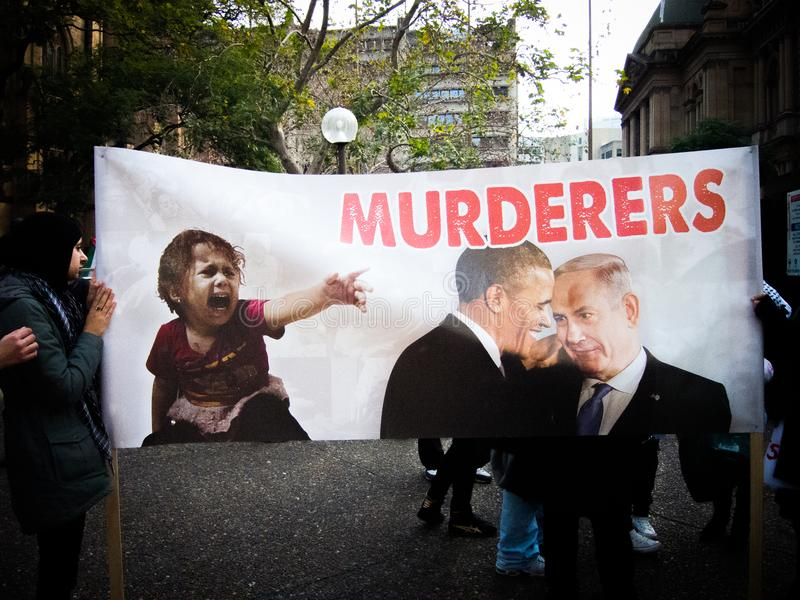 De protesteerder toont de grote affiche `-Moordenaars ` met Beeld van voorzitter Obama en de voorzitters van Israël zegt stock foto