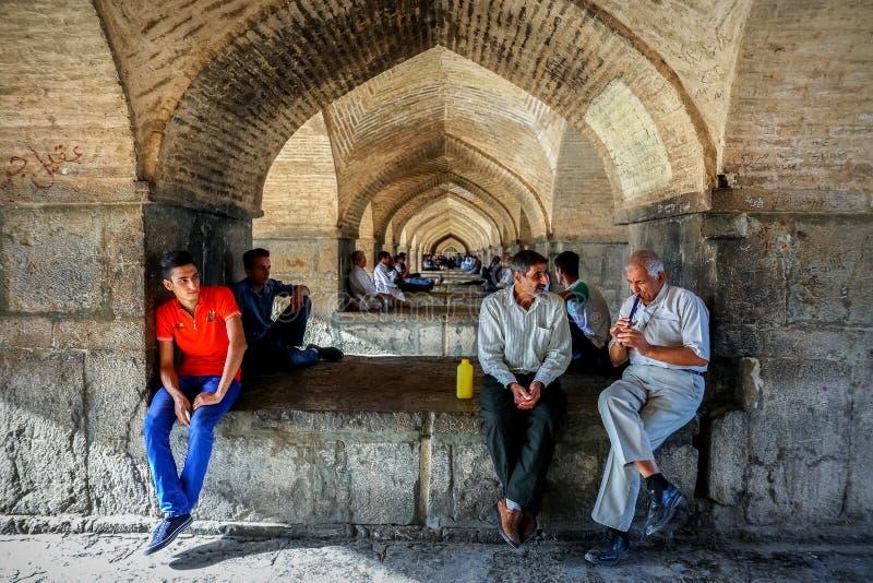 De Provincie van Iran, Isphahan, Esfahan, Khajoo-Brug, Khaju - September 2016: Een groep lokale mensen die dichtbij de boogbrug r stock fotografie