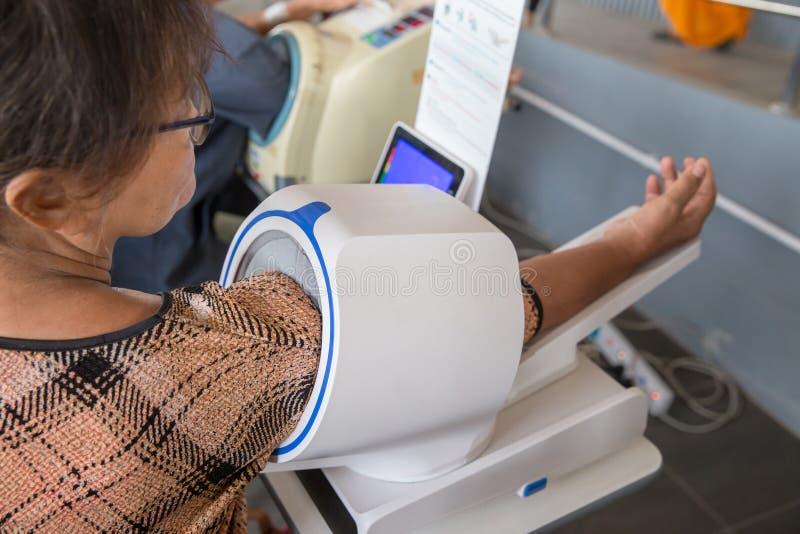 De pumpade manschettåtstramningarna mot den brachial artären med luftar pressar Digital blodtryck, Själv-mätning av blodtryck Kon royaltyfri bild