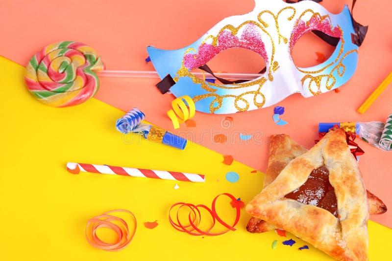 De Purimachtergrond met Carnaval-masker, partijkostuum en hamantaschen koekjes stock foto's