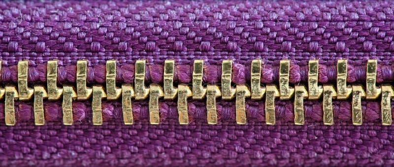 De purpere en gouden strak gesloten ritssluiting samenbindend twee lagen van stoffentextiel onder hoge vergroting detailleert dic royalty-vrije stock afbeelding