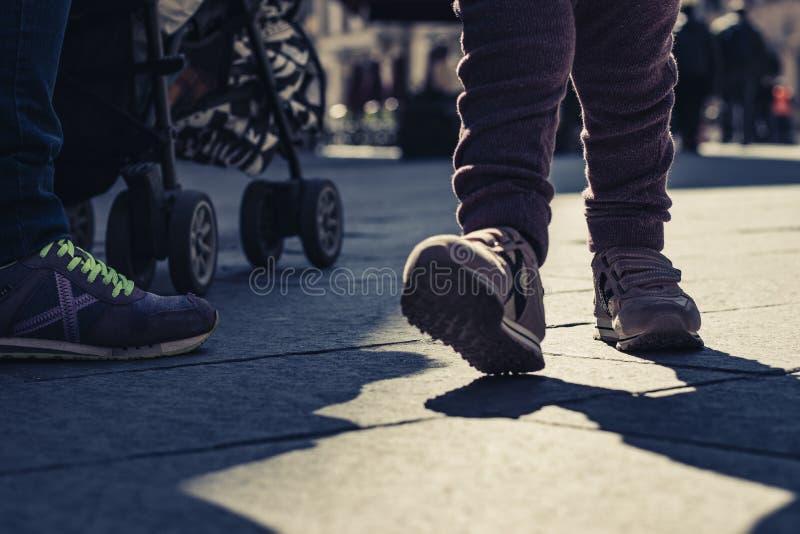 De purpere schoenen die van het babymeisje op een openluchtstraat lopen stock foto