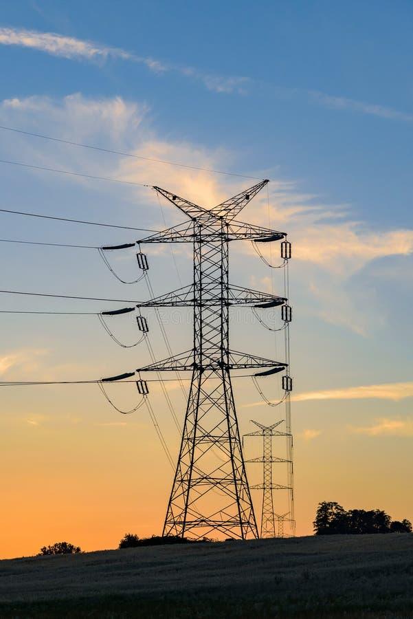 De pylonen en de lijnen van de elektriciteit bij zonsondergang stock fotografie