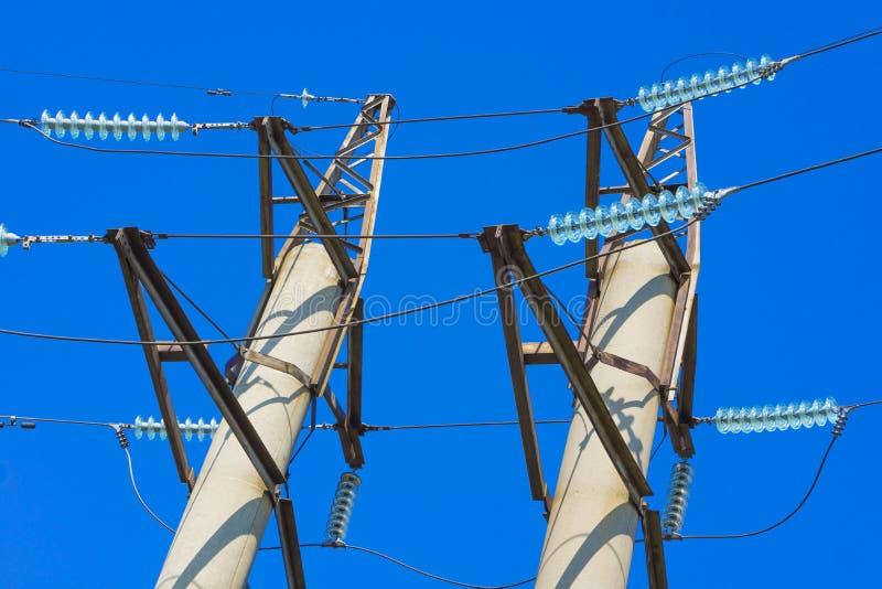 De pylonen van de hoogspanningsmacht tegen blauwe hemel stock afbeeldingen