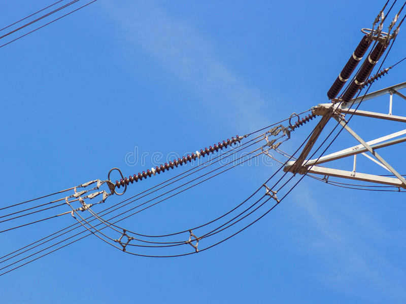 De pylonen van de hoogspanningsmacht tegen blauwe hemel stock foto
