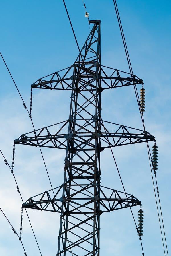 De pylonen van een hoogspanningsmacht tegen blauwe hemel en zonstralen stock foto's