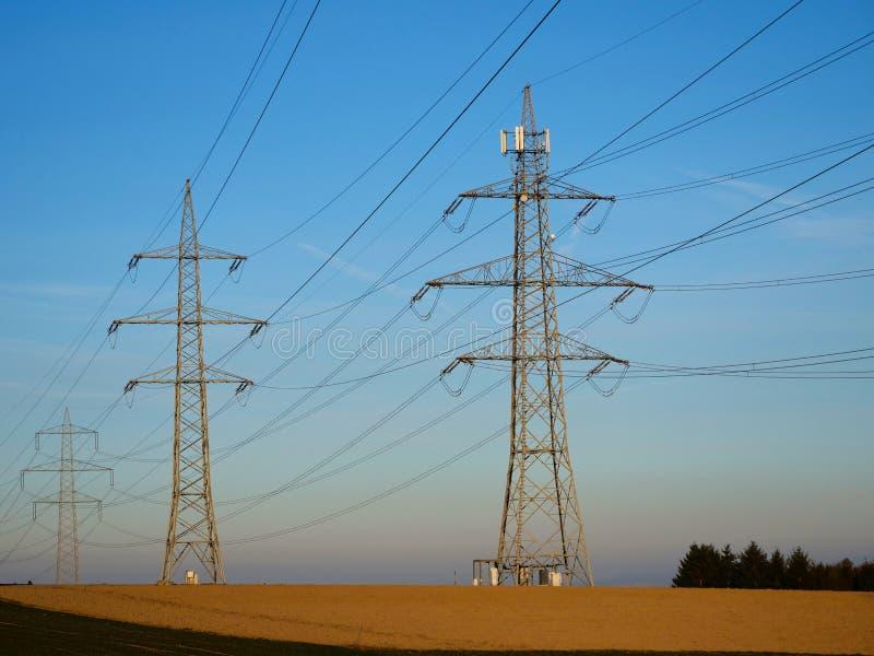 De Pylonen van de hoogspanningsmacht en Blauwe Hemel in het Platteland royalty-vrije stock foto's