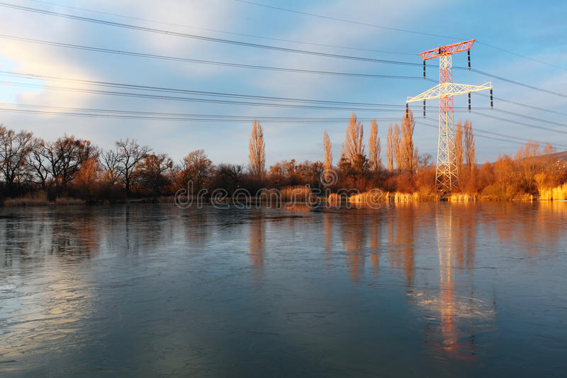De pyloon van de elektriciteit met bezinning stock fotografie