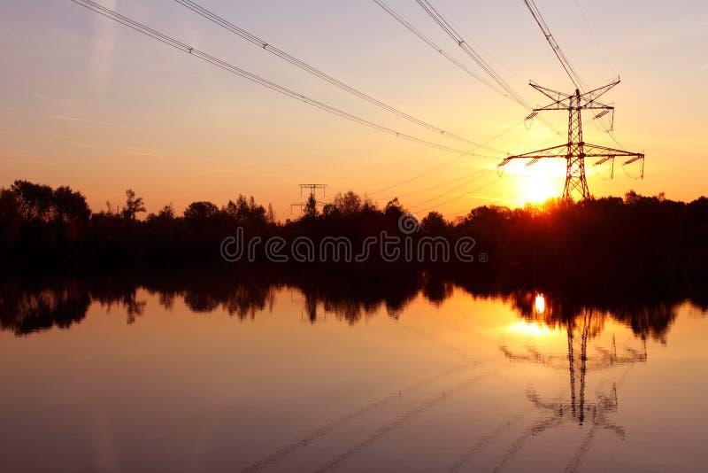 De pyloon van de elektriciteit met bezinning in water stock afbeeldingen