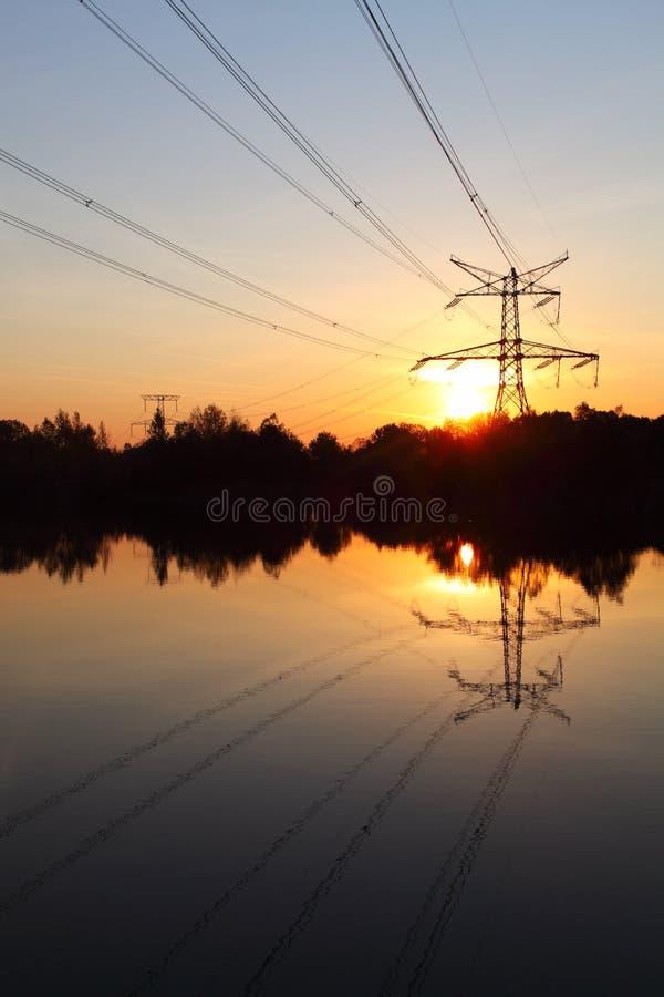 De pyloon van de elektriciteit met bezinning in water stock afbeelding