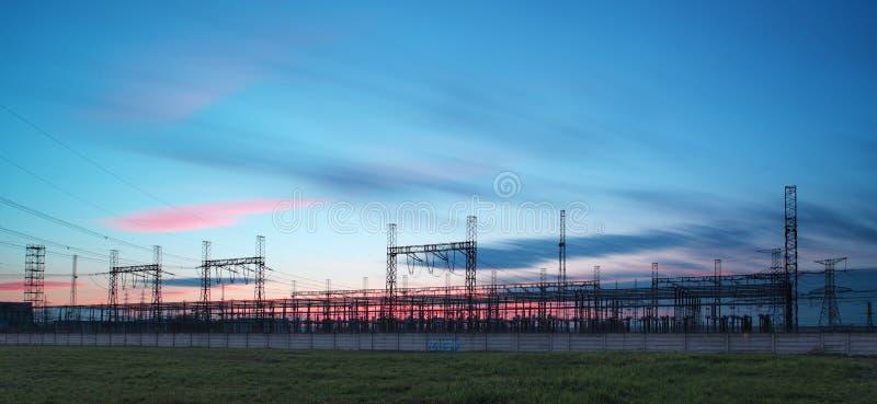 De pyloon van de elektriciteitstransmissie tegen blauwe hemel bij D wordt gesilhouetteerd die royalty-vrije stock afbeeldingen