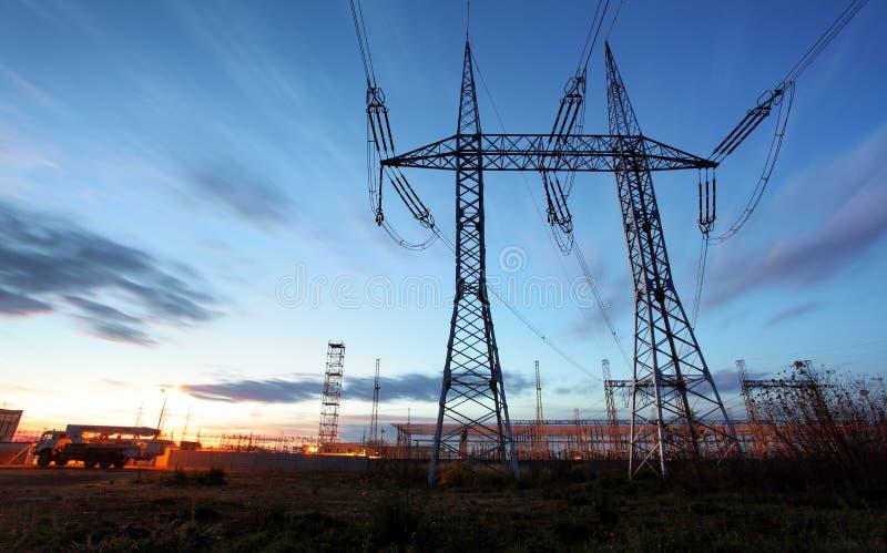 De pyloon van de elektriciteitstransmissie tegen blauwe hemel bij D wordt gesilhouetteerd die royalty-vrije stock foto's