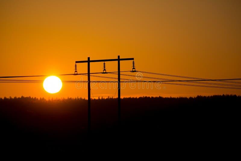 De pyloon van de elektriciteit bij zonsondergang stock foto's