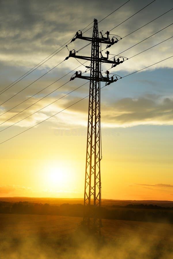 De pyloon van de hoogspanningsmacht bij zonsondergang stock foto's