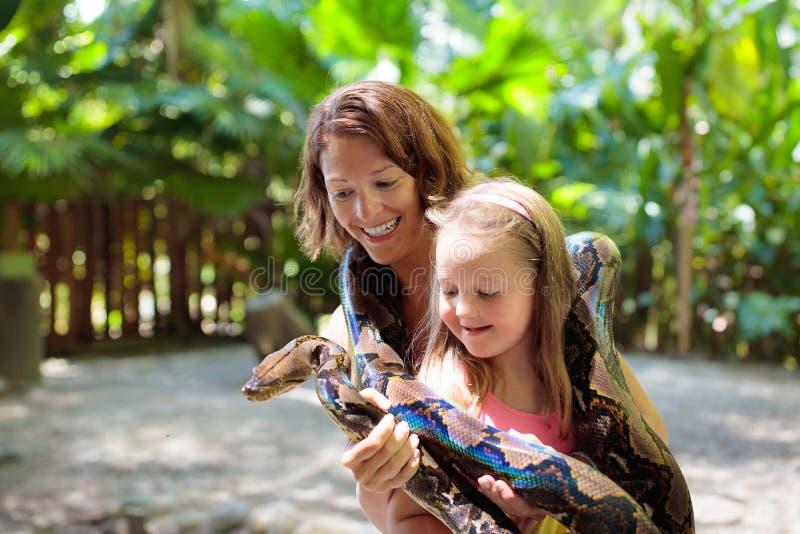 De pythonslang van de jonge geitjesgreep bij dierentuin Kind en reptiel royalty-vrije stock foto's