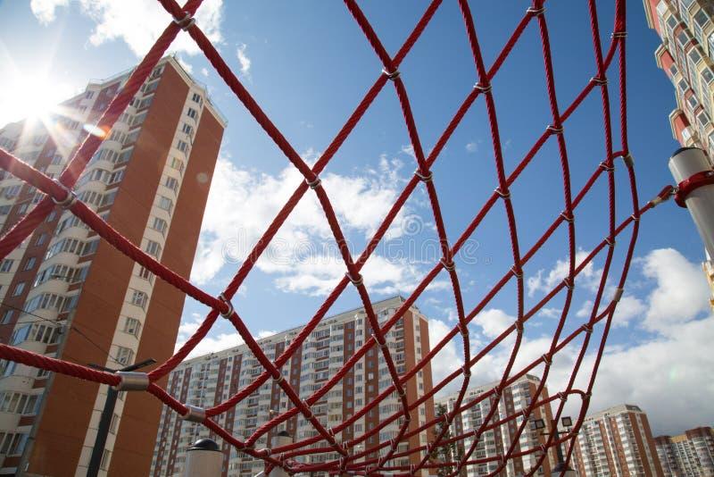 De röda repen i form av rengöringsdukhus på bakgrunden i panelljuset av inställningssolen Stads- enviro för barnsporthobbyer royaltyfri foto