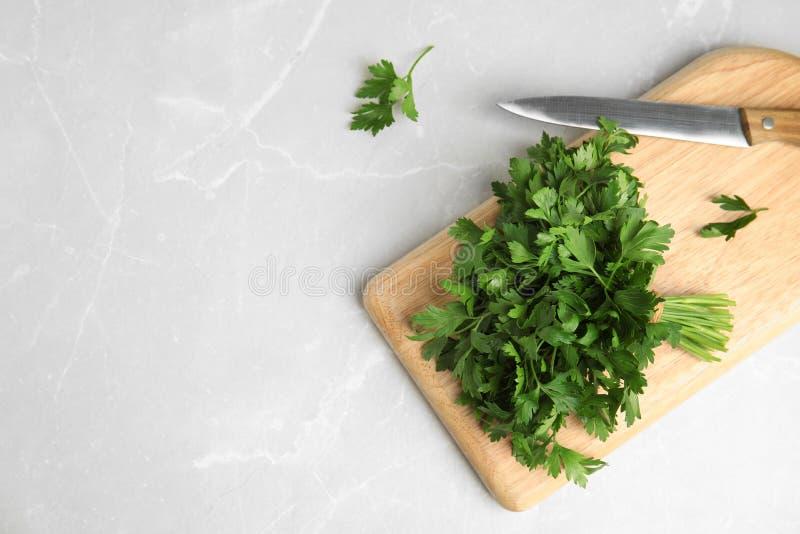 De raad met verse groene peterselie en het mes op lichte vlakke achtergrond, leggen royalty-vrije stock foto