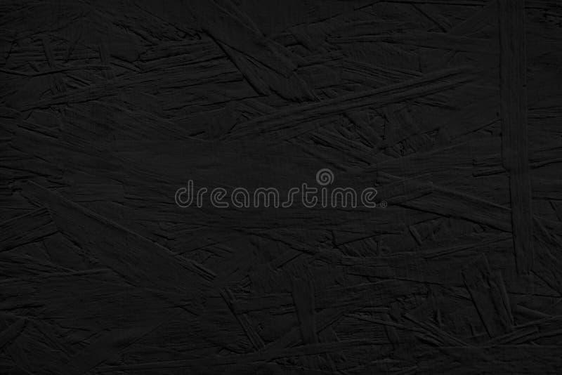 De raad schilderde van zwarte kleur De donkere achtergrond van de de muurtextuur van OSB houten stock foto's