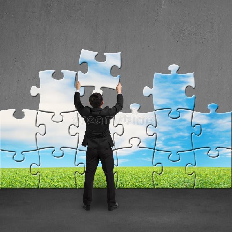 De raadsels van de zakenmanholding aan assemblage over concrete muur royalty-vrije stock foto