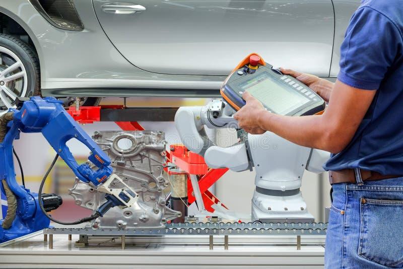 De radio van het technicusgebruik ver voor het plaatsen van programma voor controle industriële robot stock fotografie