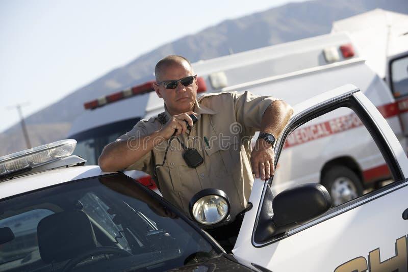 De Radio van politiemanusing two way stock afbeeldingen