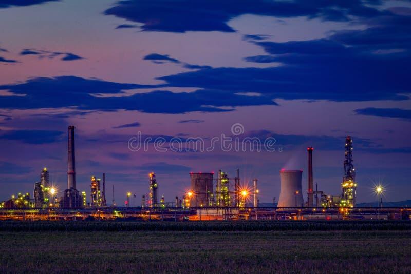 De raffinaderij van de benzineolie dichtbij een gecultiveerd gebied bij schemer wordt gevestigd die royalty-vrije stock foto