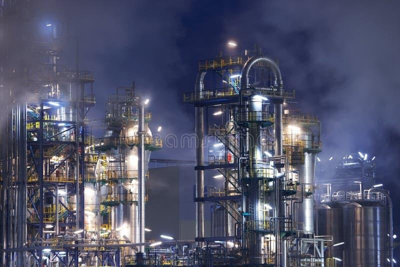 De raffinaderij van de olie met rook stock afbeelding