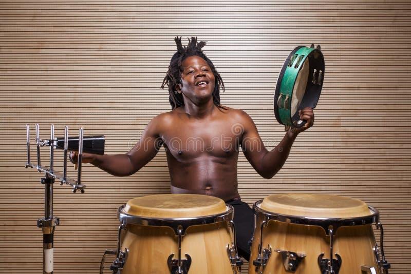 de rastafarian mens speelt conga, de tamboerijn en de koebel stock afbeelding