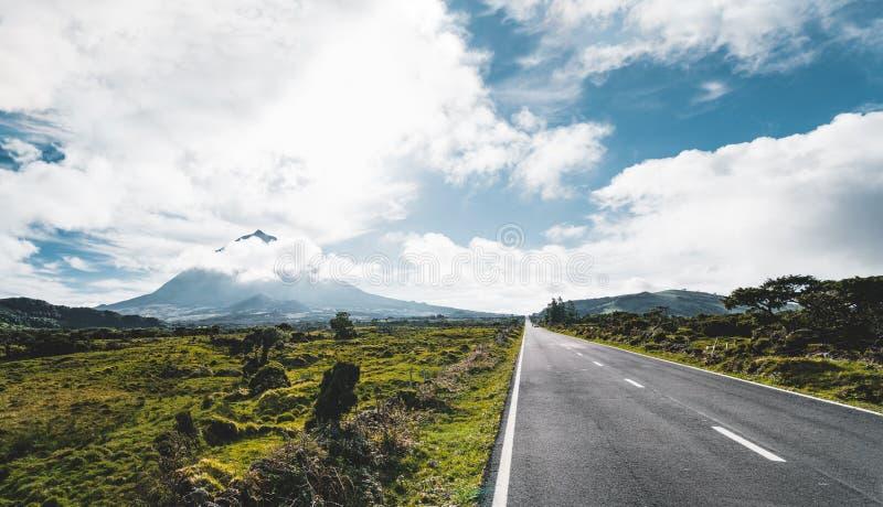 De rechte longitudinale weg van EN3 ten noordoosten van Onderstel Pico en het silhouet van het Onderstel Pico, Pico-eiland, de Az royalty-vrije stock foto